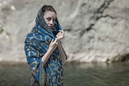 The girl of the European appearance poses in the Indian sari at Kaindy lake Stock Photo