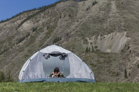 The girl looks out of tent and has a rest
