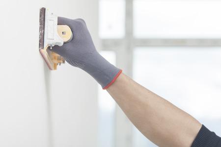 The repairman levels walls after whitewashing Standard-Bild