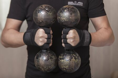 Mans hands put on sports gloves for a gym
