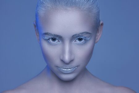 Studio beauty portrait of a beautiful girl with a makeup of snow queen
