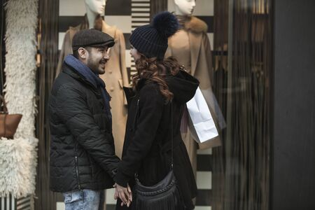 Couple window shopping outdoors in winter city street. Standing in front of a store window and looking inside. Wearing warm clothes