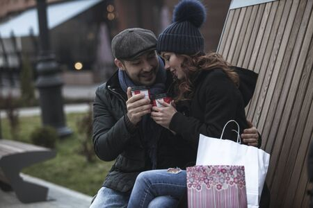 Young shopping couple drinking coffee and looking very happy