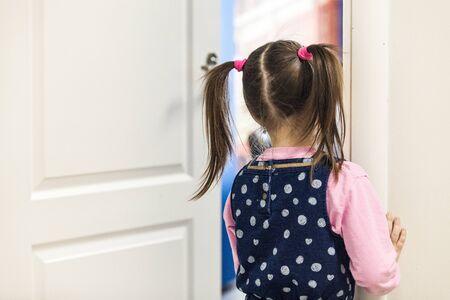 Girl (5-7) looking into classroom through the door rear view