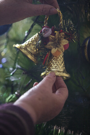 Hands of older woman decorating Christmas tree