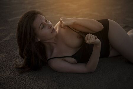 Portrait of a beautiful topless woman with wet hair and body, lying in the sand.