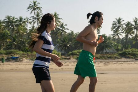 Couple running at the Vagator Beach, Goa, India