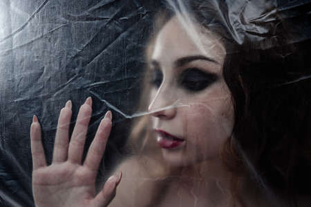 Young beauty sad woman trapped behind a plastic sheet as protection against COVID-19. Nicely fits for book cover