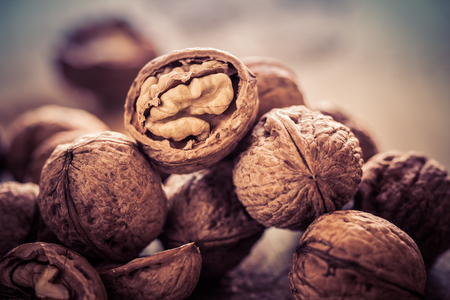 Walnuts on a wooden table in retro style. Stock Photo