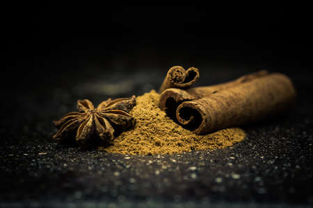 the close range: Star anise, cinnamon and ground cinnamon from close range on a black background