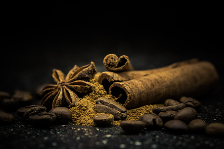 the close range: Star anise, cinnamon, coffe and ground cinnamon from close range on a black background Stock Photo