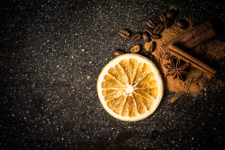 the close range: Star anise, cinnamon, coffe, orange and ground cinnamon from close range on a black background Stock Photo