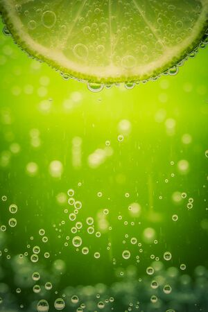 macro: Closeup of the texture of sliced lime in the water with bubbles