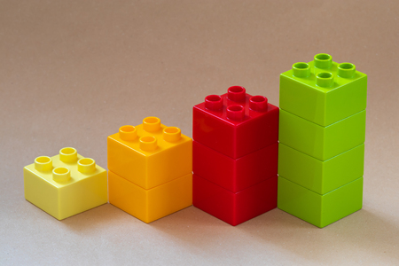 Growing bar chart from color toy blocks on beige background. Closeup.