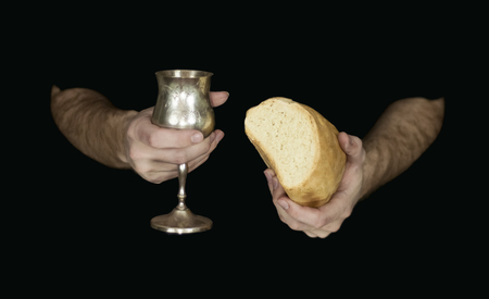 catholic mass: Two hands holding bread and wine for communion, isolated on black