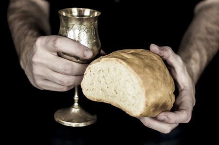 Two hands holding bread and wine for communion, isolated on black