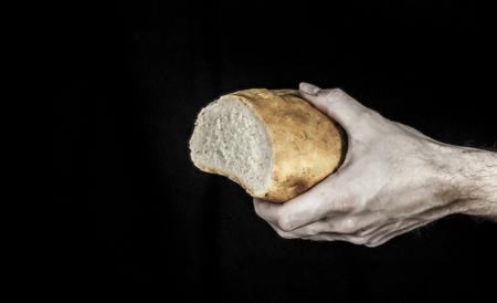 cristianismo: Una mano que sostiene una barra de pan aislado en negro