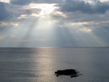 Sun shining through clouds over the sea photo