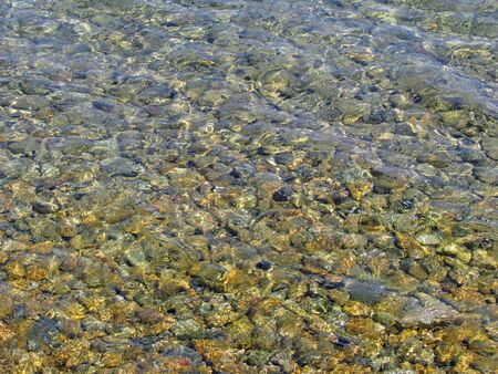 Clear shallow water of a pebble beach