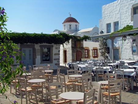 chora: City square café with a church behind Editorial
