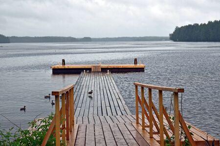 dock, ducks and rainy day Stock Photo