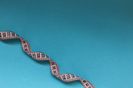 twisted centimeter tape on a blue background