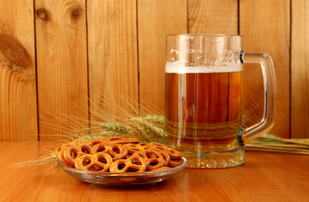 on the table is a foam beer in a mug and a pretzel in a plate Banco de Imagens
