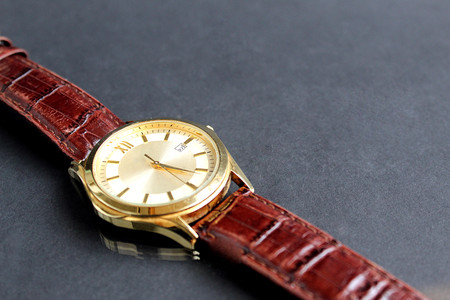 men's watch with a brown strap on a black background