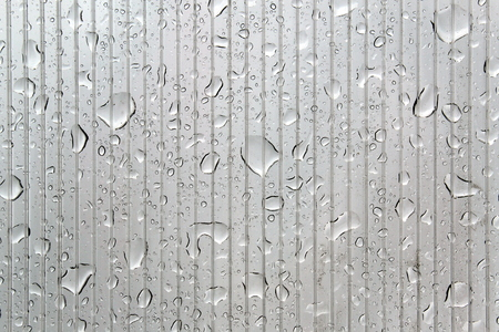 A lot of water drops on a striped transparent surface
