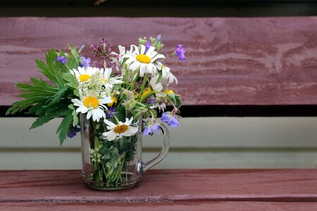 There is a cup with wild flowers on the table