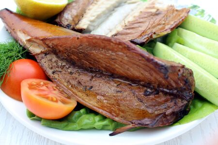 Smoked mackerel on a plate. mackerel with lemon and vegetables