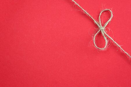 Background with the bow-knot of the rope. Tie boxes for gifts. Jute rope with bow. Twine.