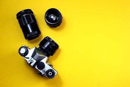 Retro camera. Old film camera with lenses on a yellow background