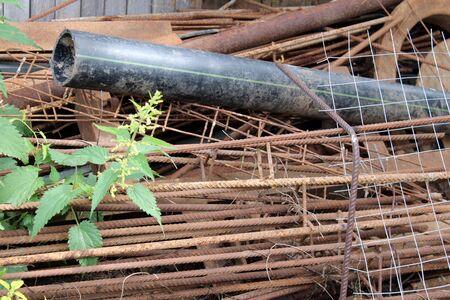 Old rust metal, garbage, scrap iron lies overgrown with nettles Banco de Imagens