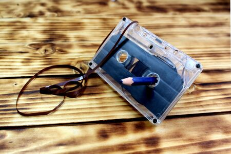 Retro audio cassette and pencil on a wooden table. Old magnetic storage medium. Stock Photo