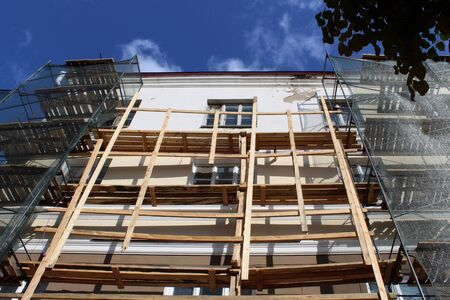 Scaffolding stands near the building to repair the house Stock fotó
