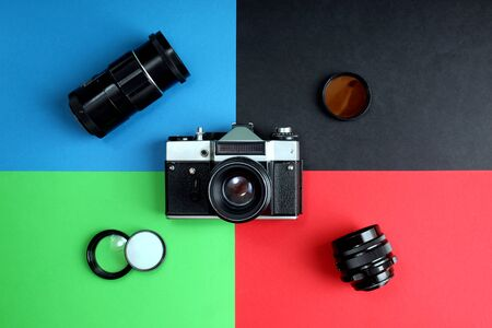 The old film camera and lenses lie on different four backgrounds