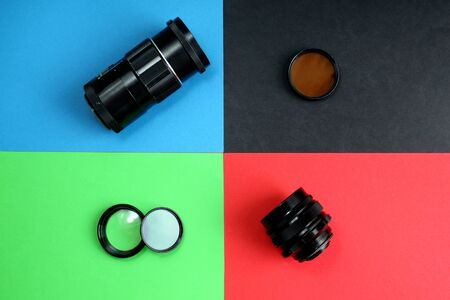 Old retro camera lenses lie on different four backgrounds