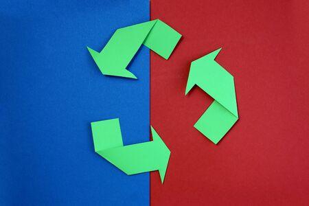 Grüne Pfeile recyceln es Symbol auf blauem und rotem Hintergrund. Symbol für recyceltes Material