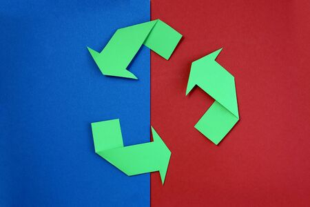 Green arrows recycle it symbol on a blue and red background. recycled material symbol