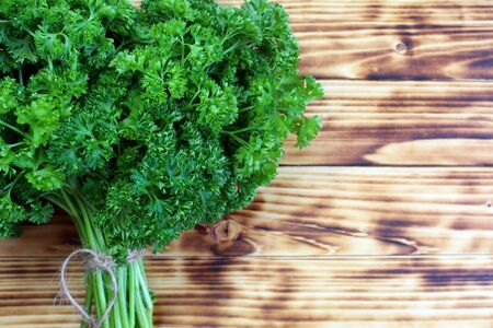 lush bouquet of fresh parsley lies on the table Stock Photo
