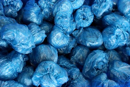 in a heap are rolled up disposable blue shoe covers Stock Photo