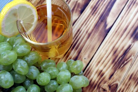 Glass of fresh grape juice with grapes on the background Stock Photo