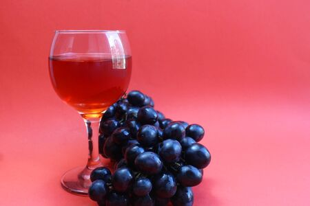 one glass of black grape wine on a red background