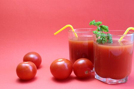 tomato juice in a glass with straws surrounded by tomatoes