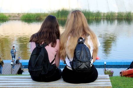 two girls sit with their backs on the riverbank and gossip