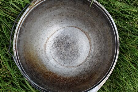an empty cooking pot on the street stands on the lawn in the grass