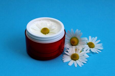 face cream with chamomile extract on a blue background