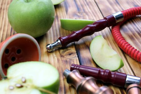 red hookah stands surrounded by green apple slices on a wooden