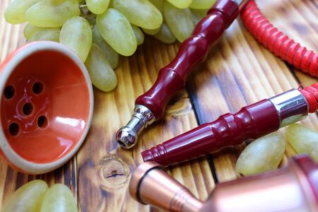 red hookah stands surrounded by green grapes on a wooden Stock Photo